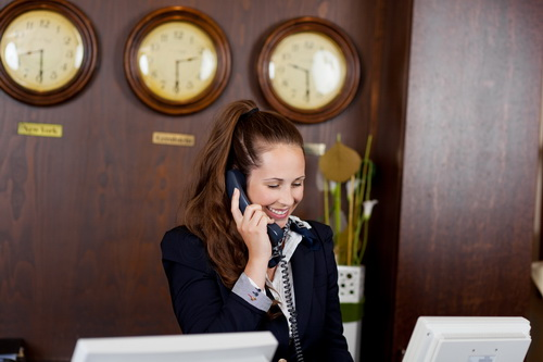 Smiling receptionist taking a telephone call